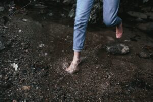 Woman walking barefoot in stream
